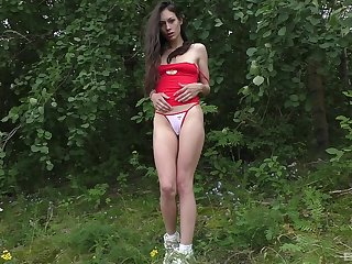 Skinny brunette drops her panties to poke her cunt in the outdoors